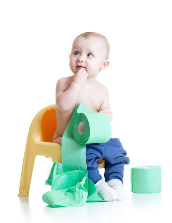 potty: toddler sitting on chamber pot with toilet paper rolls Stock Photo