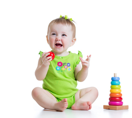 toddler girl boy plays with colorful toy pyramid photo
