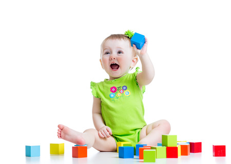 happy toddler child girl playing wooden toy blocks isolated on white photo