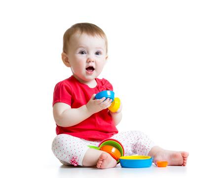 bambin enfant qui joue avec des jouets de couleur isolé sur blanc Banque d'images