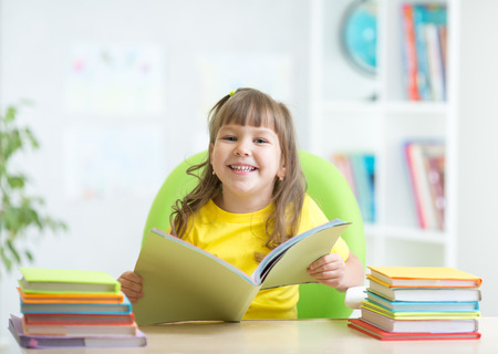 primary colors: Happy kid girl with opened book in primary school Stock Photo