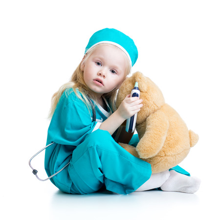 pediatric nurse: kid girl playing doctor with plush toy isolated on white