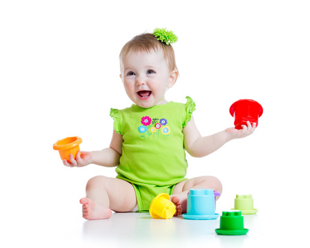 babies playing: smiling child girl playing with color toys isolated on white