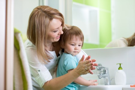 child boy and mother washing hands with soap in bathroom
