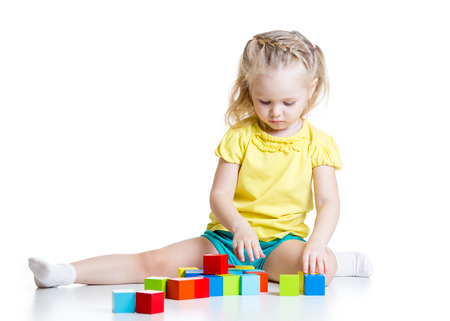 kid girl 3 years old playing  wooden cubes isolated on white photo