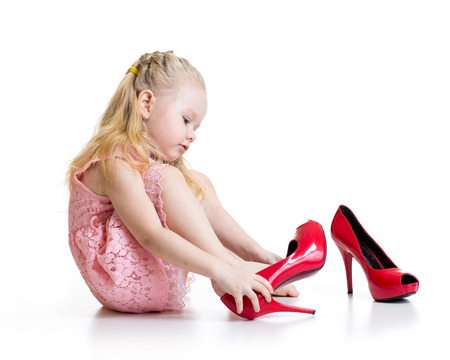 put: Little blond girl trying big mother shoes on