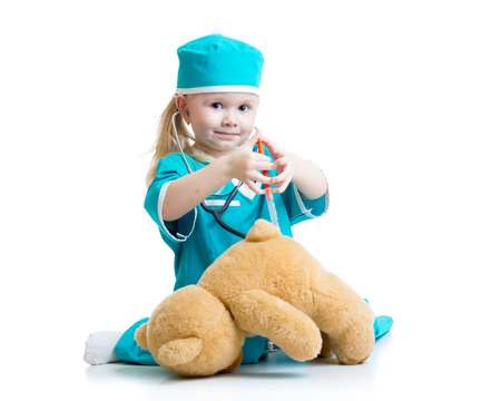 Chica niño con la ropa del doctor que juegan el juguete de felpa