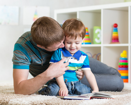 father reading children book to little son Stock Photo
