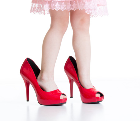 big and small: Little child girl playing with mommy red shoes Stock Photo