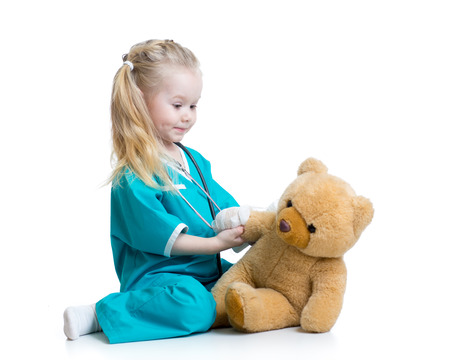 plush toy: child girl playing doctor with plush toy isolated