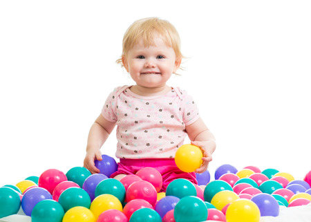 Little girl in ball pit with colored balls isolated