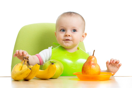little child girl sitting at table with fruits isolated