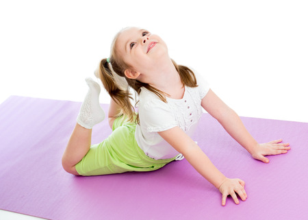 Kid doing fitness exercises on mat isolated Stock Photo
