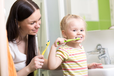mother teaching child teeth brushing in bathroom photo