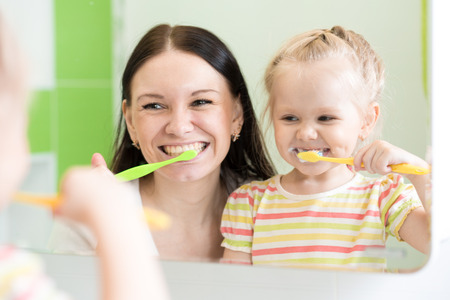 tooth cleaning: Hygiene. Happy mother and child girl brushing teeth together Stock Photo