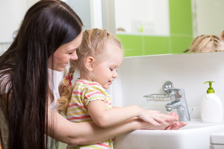 kid and mother washing hands with soap in bathroom