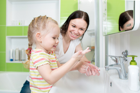 wash hands: Happy mother and child washing hands with soap together in bathroom Stock Photo