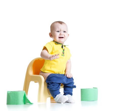 chamber pot: crying child sitting on chamber pot with toilet paper rolls