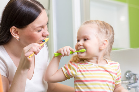 cute mom teaching kid teeth brushing in bathroom