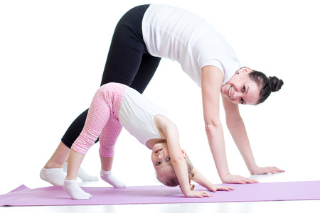 Yoga for woman and child. Mother and kid doing fitness exercise