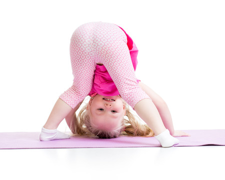 headstand: funny little girl standing on her hand isolated on white