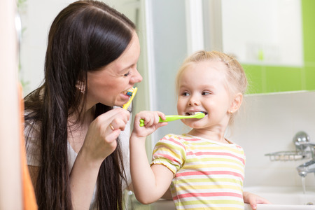 toothcare: cute mom teaching child teeth brushing in bathroom Stock Photo