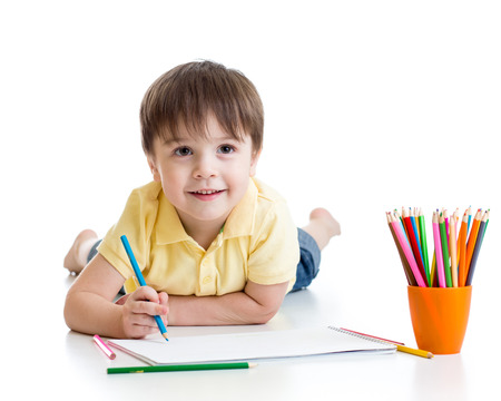 kindergarten education: Cute child little boy drawing with pencils isolated on white