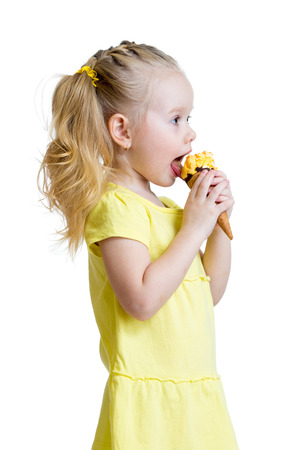 licking in isolated: happy kid girl eating ice-cream in studio isolated