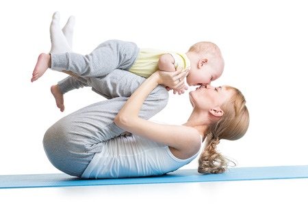 young mother does fitness exercises together with kid boy isolated