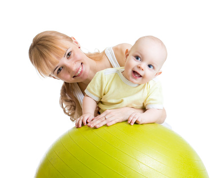 pretty smile: mother and her baby boy having fun with gymnastic ball