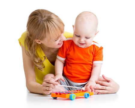 parental: smiling child boy and mom playing with musical toy