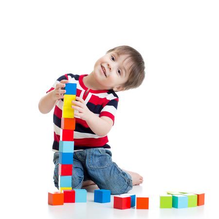 bambin enfant garçon jouant blocs de jouets en bois isolé