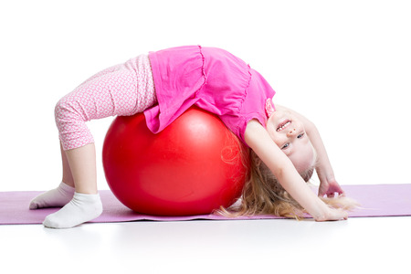 ball stretching: Cute kid girl stretching on pilates fitness ball