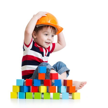 Kid boy as a construction worker in protective helmet on white background photo