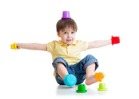 children playing with toys: smiling child boy having fun with color toys isolated on white Stock Photo