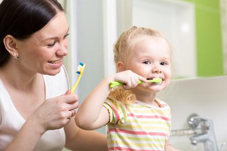 milk tooth: cute mother teaching kid girl teeth brushing