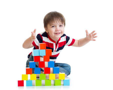 pleased kid boy playing toy blocks isolated photo