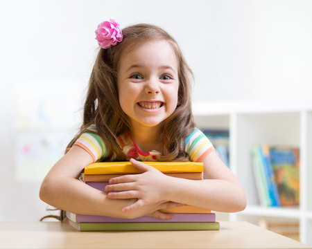 Prodigy: Cute kid girl preschooler with books indoor Zdjęcie Seryjne