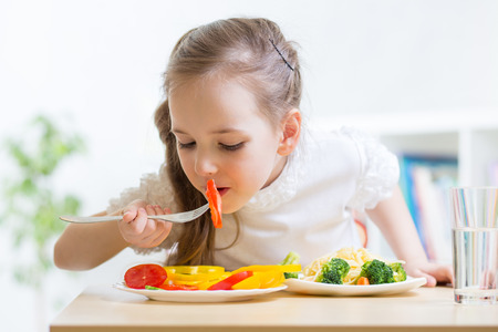 hungry kid: child girl eating healthy food at home Stock Photo