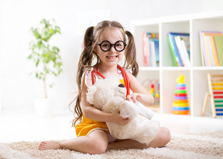 doctor toys: child girl playing doctor and curing plush toy indoors Stock Photo