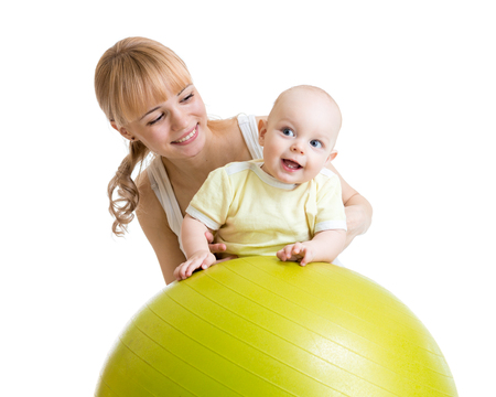 playschool: mother and her baby boy having fun with gymnastic ball