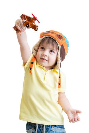 heureux jeune garçon habillé pilote et jouant avec avion jouet en bois