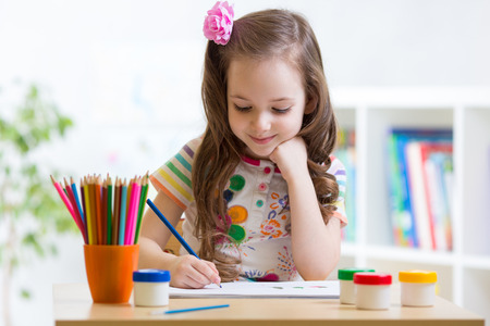 preschool: Cute preschooler child girl drawing pencil at home Stock Photo