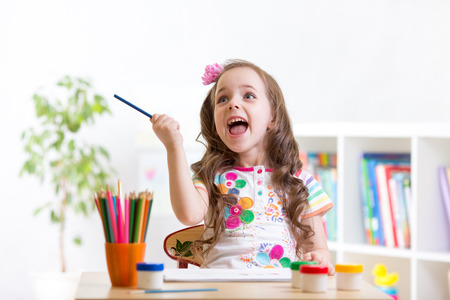 center table: Cheerful child little girl drawing with pencils in preschool