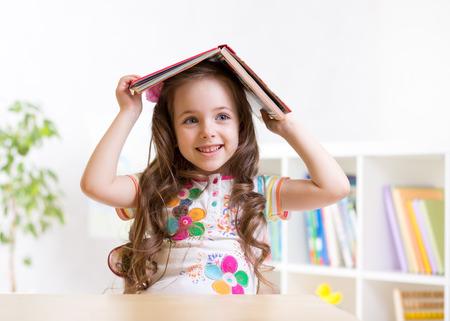 enfant d'âge préscolaire fille d'enfant avec le livre sur sa tête à l'intérieur