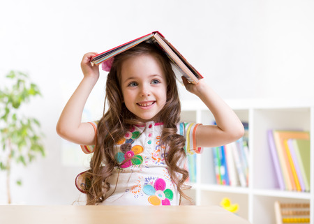 preschooler  kid girl with book over her head indoors
