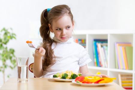 jolie jeune fille refusant de manger ses repas sain de légumes Banque d'images
