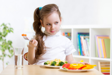 bore: pretty kid girl refusing to eat her dinner healthy vegetables