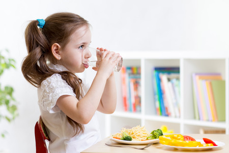 children breakfast: Cute kid girl drinking water sitting at table in home Stock Photo