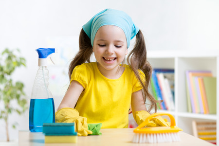 casita de dulces: la niña linda que hace la limpieza en la habitación de los niños en el hogar Foto de archivo